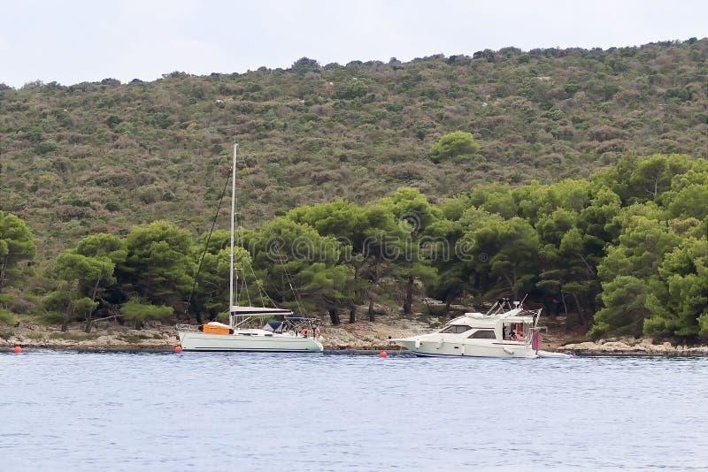Een modern varend jacht wordt verankerd in een baai De mensen baden in het overzees Actieve rust op het Adriatische Overzees van  stock afbeeldingen