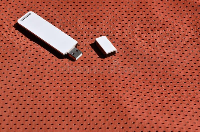 Een moderne draagbare adapter van USB wordt WiFi op de rode die sportkleding geplaatst van polyesternylon fibe wordt gemaakt stock foto