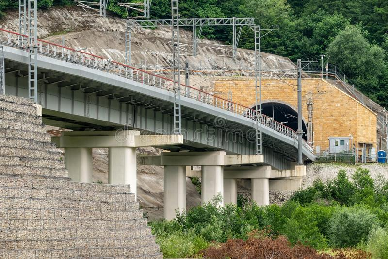 Een moderne spoorwegbrug leidt tot een tunnel in de berg stock foto's