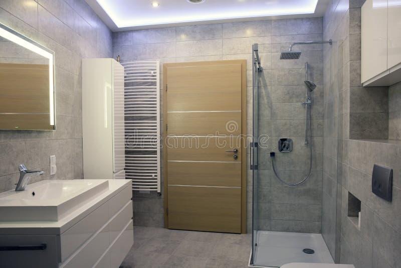 Een moderne stijlbadkamers met grijze tegels stock afbeeldingen
