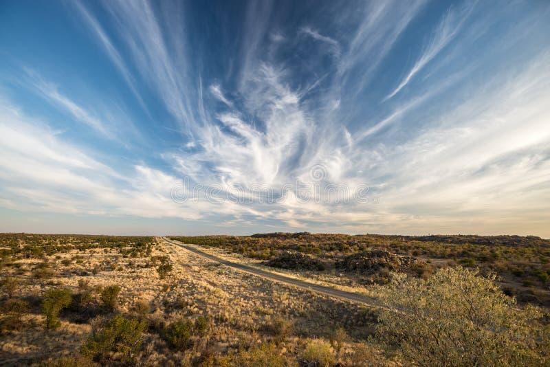 Een moderne weg over Namibian eindeloze vlaktes met magische hemel royalty-vrije stock foto