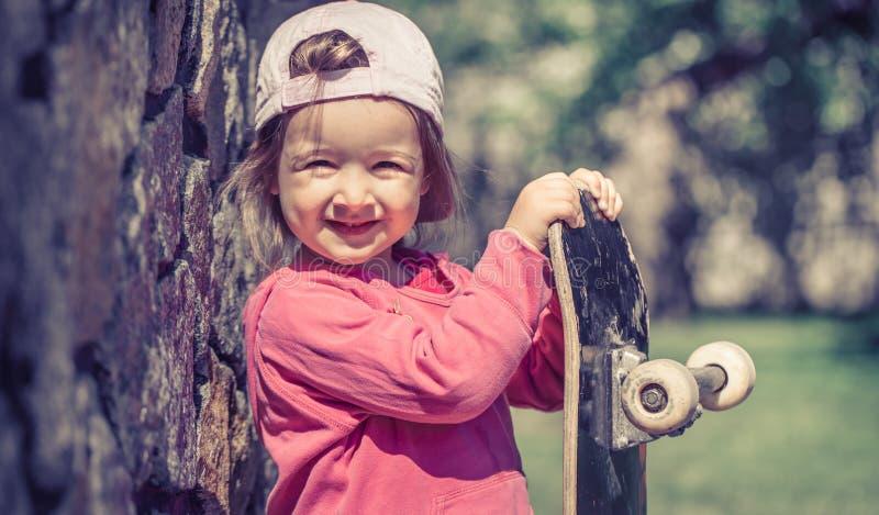 Een modieus meisje houdt een skateboard en speelt ou stock foto's