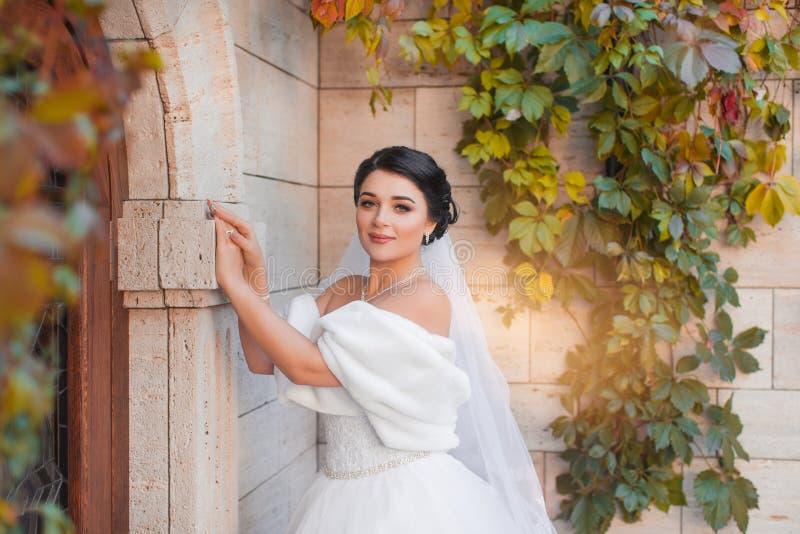Een modieuze bruid bevindt zich door de bakstenen muur royalty-vrije stock afbeeldingen