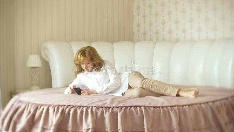 Een modieuze dame kleedde zich in een witte blouse en beige broeken Een jonge vrouw gebruikt binnen een mobiele telefoon met stock afbeeldingen