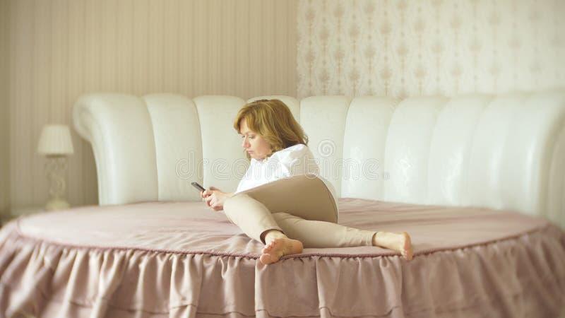 Een modieuze dame kleedde zich in een witte blouse en beige broeken Een jonge vrouw gebruikt binnen een mobiele telefoon met royalty-vrije stock afbeeldingen
