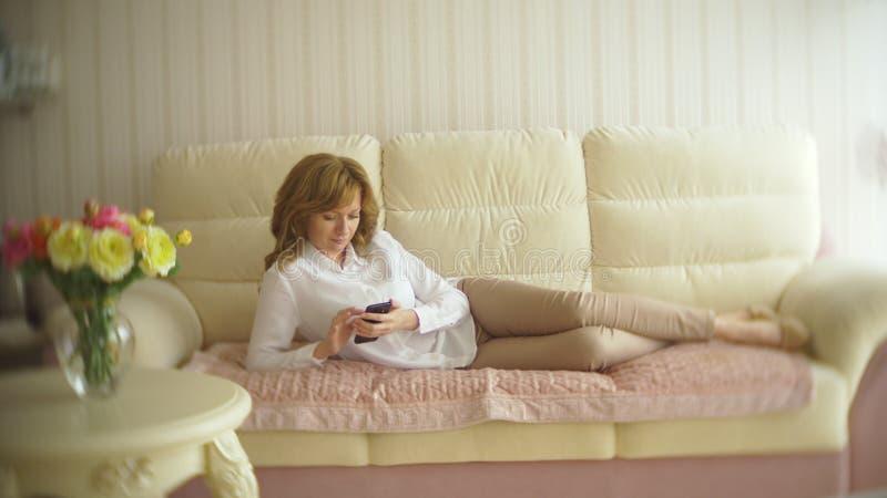 Een modieuze dame kleedde zich in een witte blouse en beige broeken Een jonge vrouw gebruikt binnen een mobiele telefoon met stock foto's
