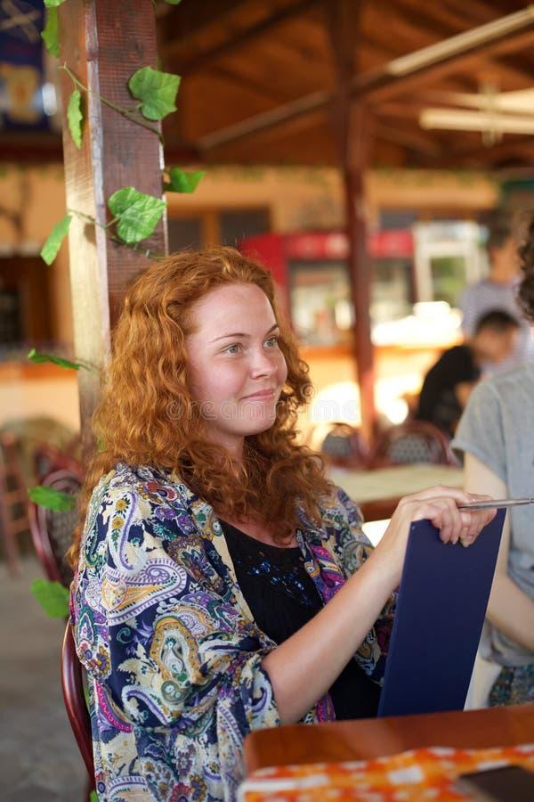 Een modieuze die dame in een kleurrijke sjaal op besprekingen wordt verpakt stock afbeeldingen