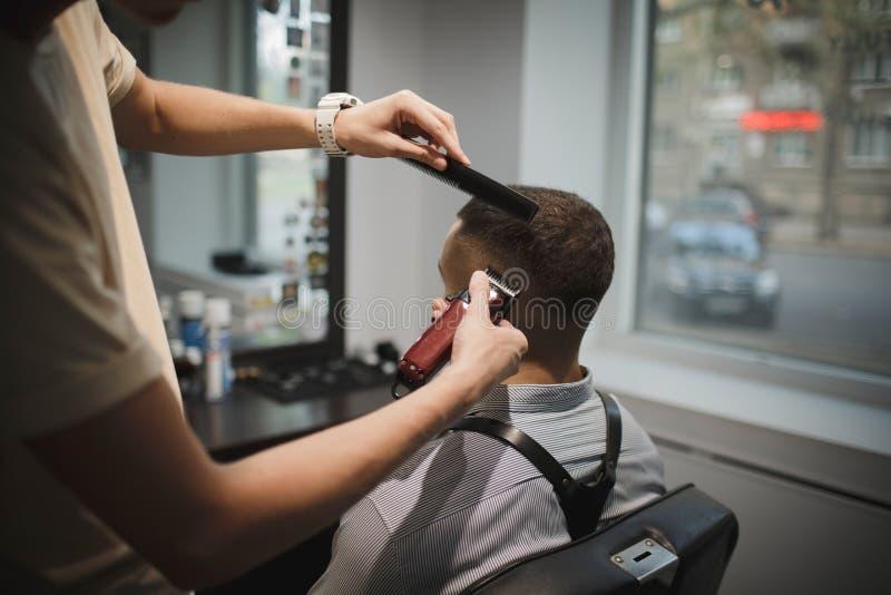 Een modieuze herenkapper dienende cliënt op een herenkapperachtergrond De kapper ` s overhandigt het scheren mannelijk cliënt` s  royalty-vrije stock foto