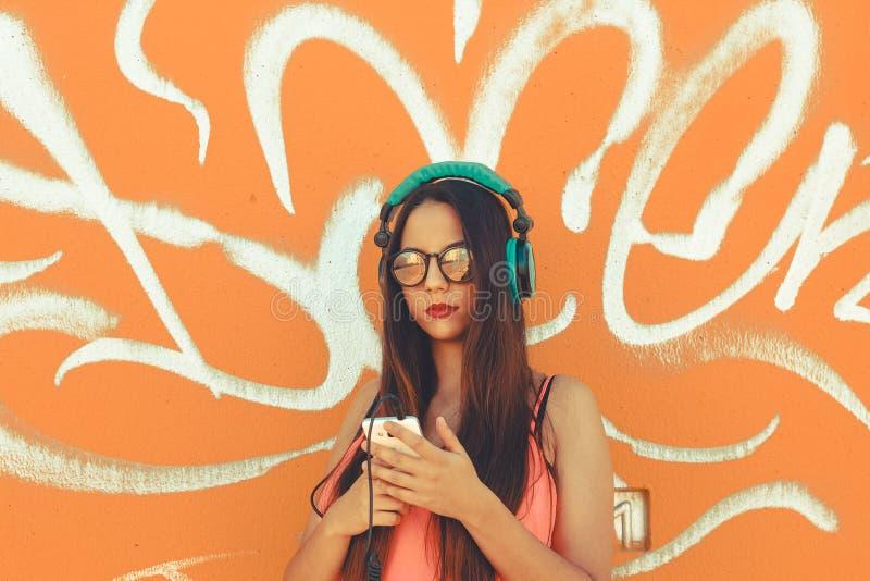 Een modieuze jonge dame die haar mobiele telefoon met behulp van om te luisteren muziek met haar hoofdtelefoons stock foto