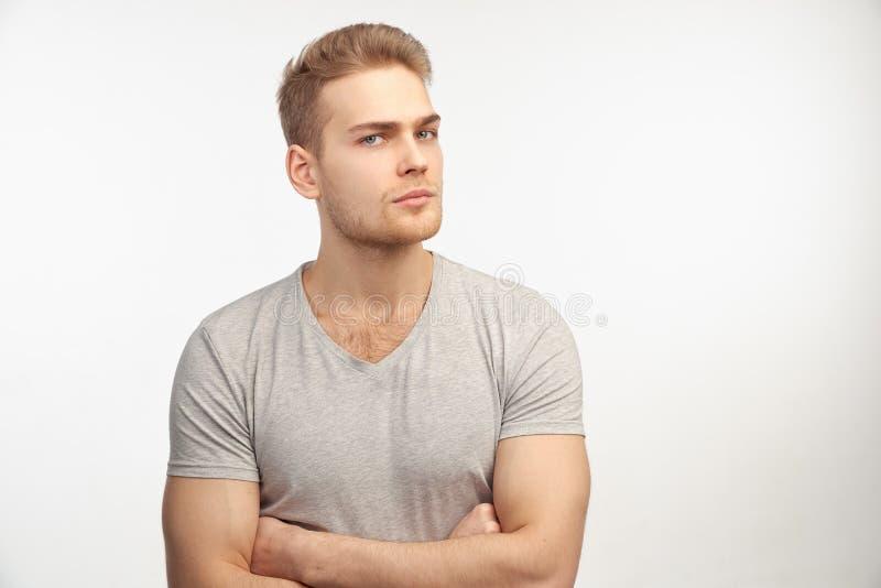 Een modieuze jonge mens van atletische bouwstijl met blond haar met een ernstige uitdrukking bekijkt de camera en denkt over iets stock afbeelding
