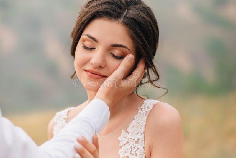 Een modieuze, mooie bruid, geniet van de aanraking van haar echtgenoot` s hand aan haar gezicht Portretfotografie royalty-vrije stock afbeeldingen