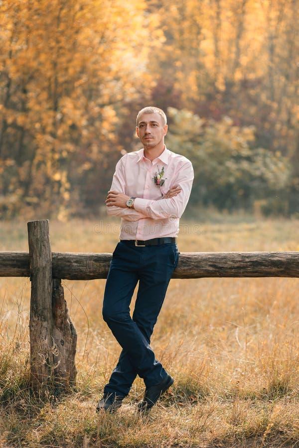 Een modieuze, volwassen, succesvolle mens bevindt zich op de achtergrond van een houten omheining De kerel is gekleed in een roze stock afbeeldingen