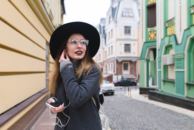 Een modieuze vrouw verbetert hoofdtelefoons in de oren tegen de achtergrond van oude architectuur royalty-vrije stock foto's