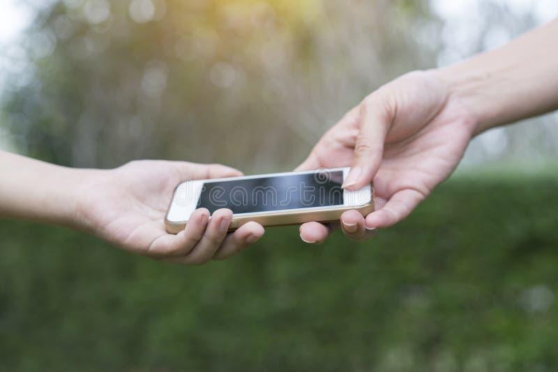 Een moeder die haar kind een mobiele telefoon geven royalty-vrije stock foto