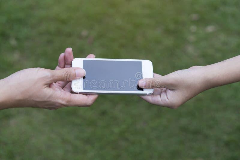 Een moeder die haar kind een mobiele telefoon geven royalty-vrije stock afbeeldingen