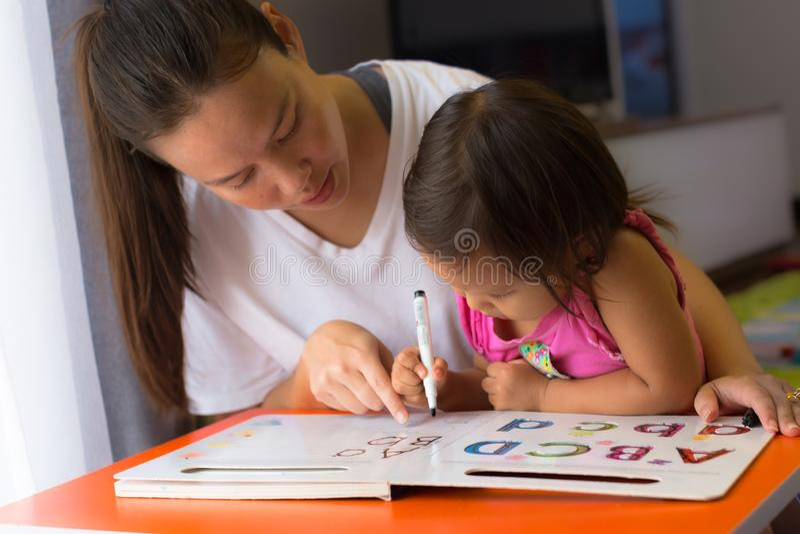 Een moeder die haar kind onderwijzen hoe te om de alfabetten te schrijven Homeschoolingsconcept Zich en jonge geitjes die concent royalty-vrije stock fotografie