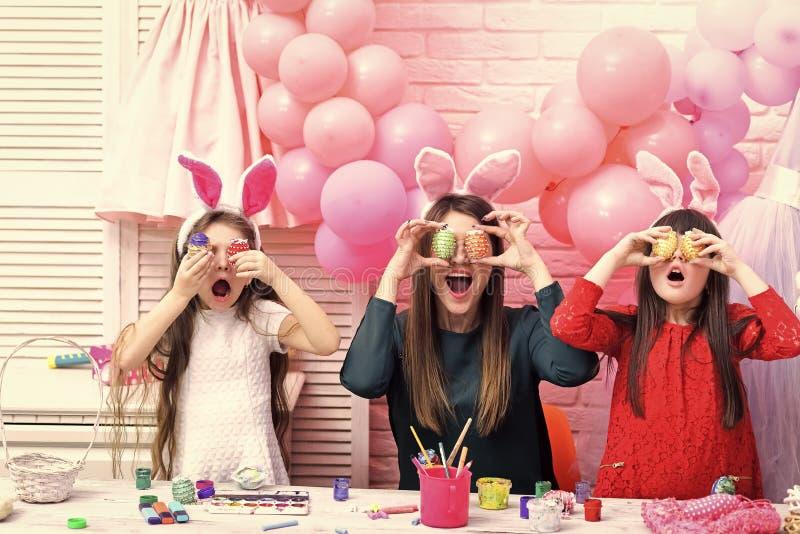 Een moeder en haar dochters schilderen eieren royalty-vrije stock afbeeldingen