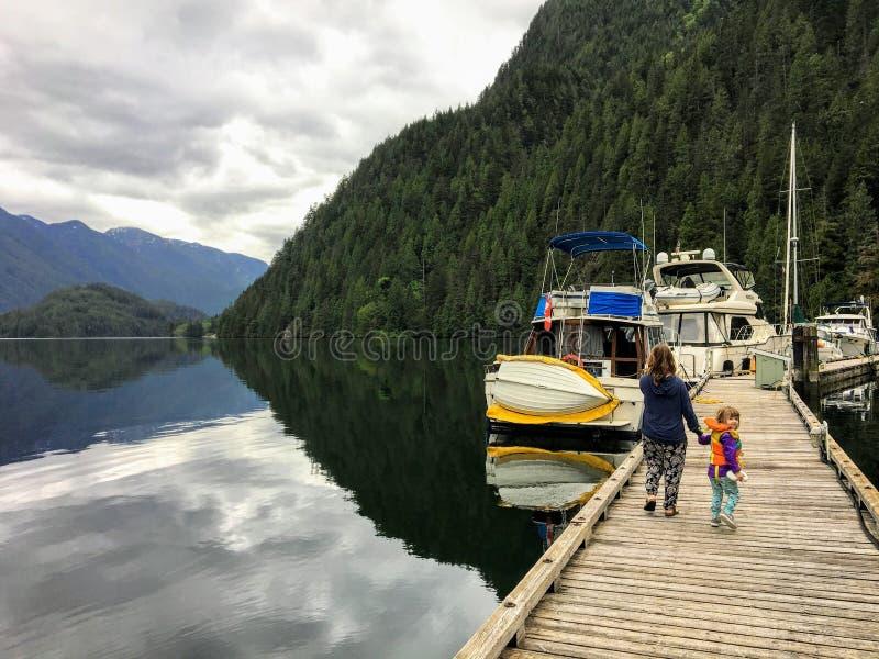 Een moeder en haar jonge de holdingshanden die van de 5 éénjarigendochter langs het dok naar hun boot lopen stock afbeelding