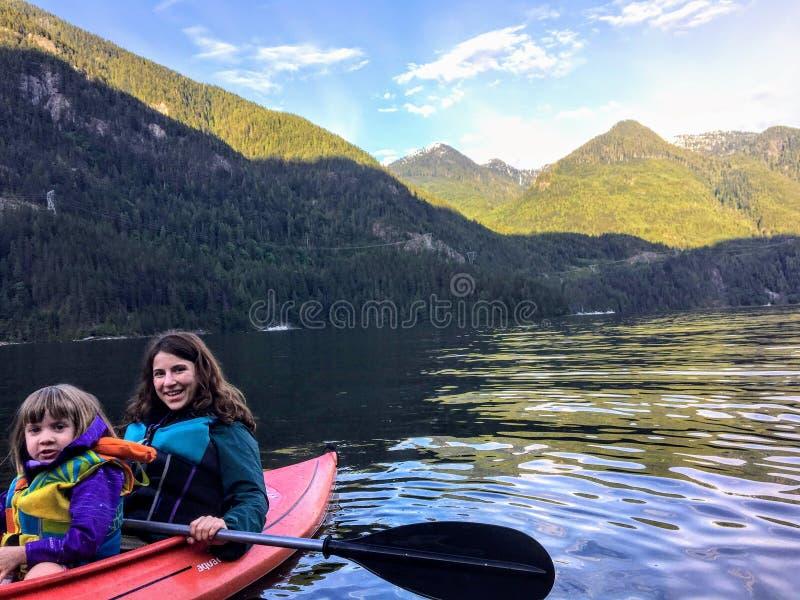 Een moeder en haar kleine dochter die samen op de oceaan in de mooie verre plaats van Indisch Wapen kayaking stock afbeelding