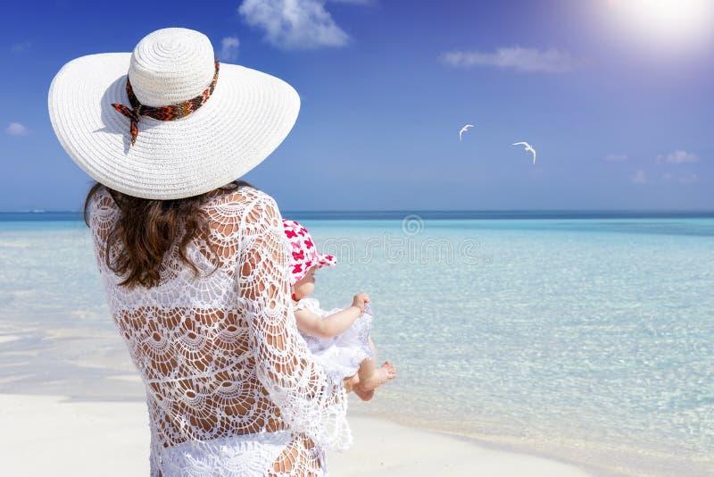 Een moeder en haar pasgeboren baby op een tropisch strand royalty-vrije stock foto's