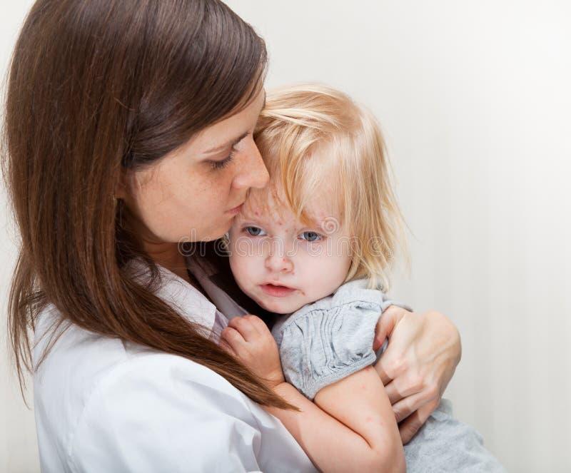 Een moeder houdt een ziek meisje. stock afbeeldingen