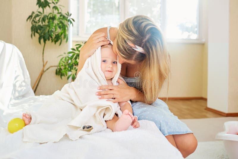 Een moeder koestert haar baby in een handdoekruimte binnen de ruimte stock afbeeldingen