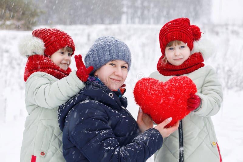 Een moeder met dochterstweelingen speelt met plucheachtig hart royalty-vrije stock foto's