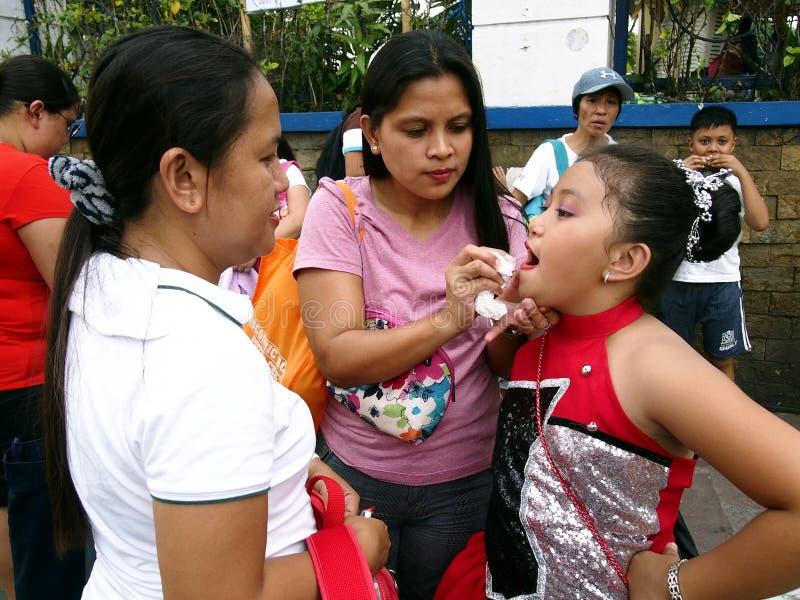 Een moeder past lippenstift toe en maakt omhoog op haar kind dat ` s een deelnemer bij een parade tijdens het Sumaka-Festival in  royalty-vrije stock afbeeldingen
