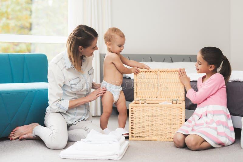 Een moeder van twee kinderen heeft pret met kinderen tijdens huis het schoonmaken Zij zijn in een heldere ruimte en zetten kleren stock foto's