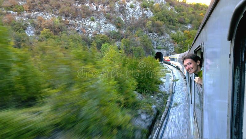 Een moedig jong meisje leunt uit de venster snel bewegende trein die de tunnel naderen Zij lacht en gelukkige reis stock afbeelding