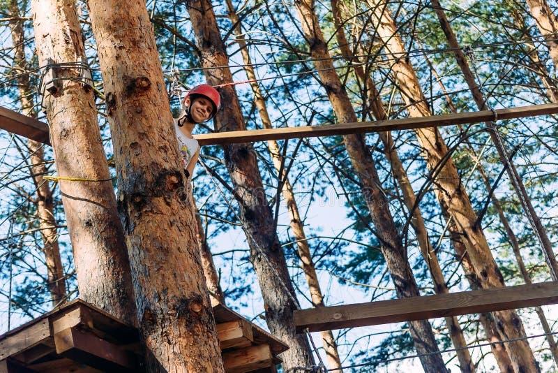 Een moedig tien-jaar-oud meisje in een beschermende helm piept uit van achter een boom op een kabelpark stock foto