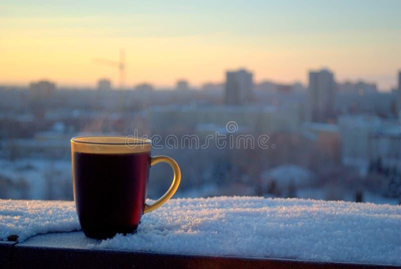 Een mok hete zwarte thee op de achtergrond van een ijzige de winterdageraad en een vaag panorama royalty-vrije stock fotografie