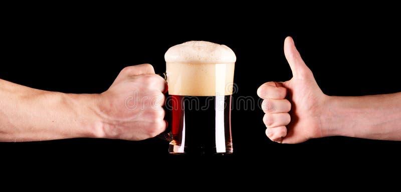 Een mok zwart bier in kerelshand Duimen op hand op zwarte achtergrond wordt geïsoleerd die stock fotografie