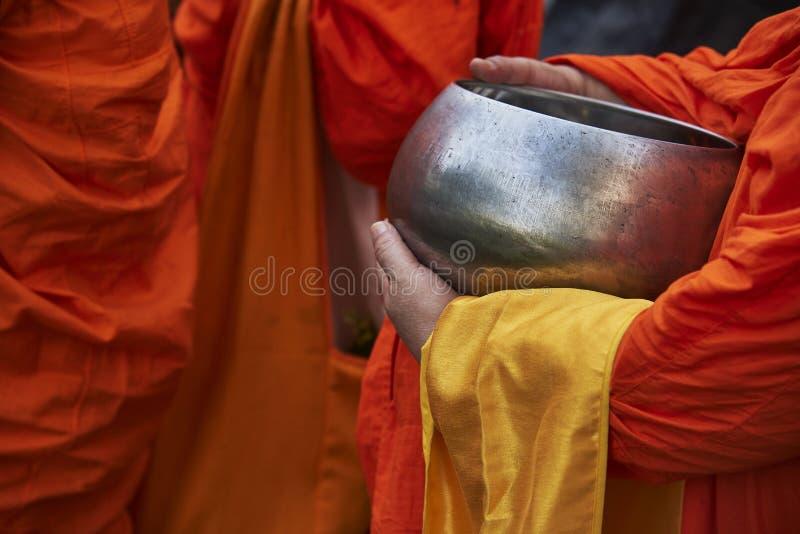 Een monnik die een aalmoeskom houden stock fotografie