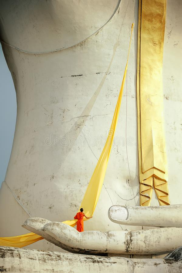 Een monnik die gele robe voor het standbeeld van Boedha voorbereiden stock fotografie