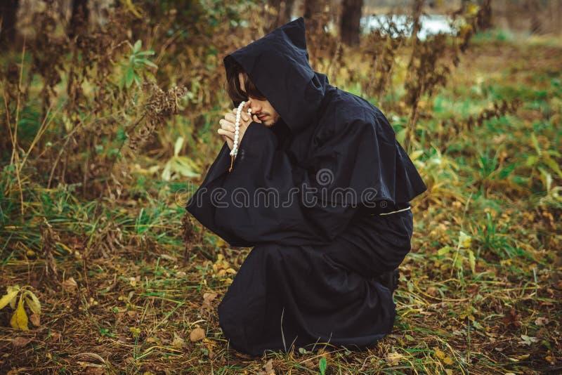 Een monnik die in robes in het hout bidden stock foto's