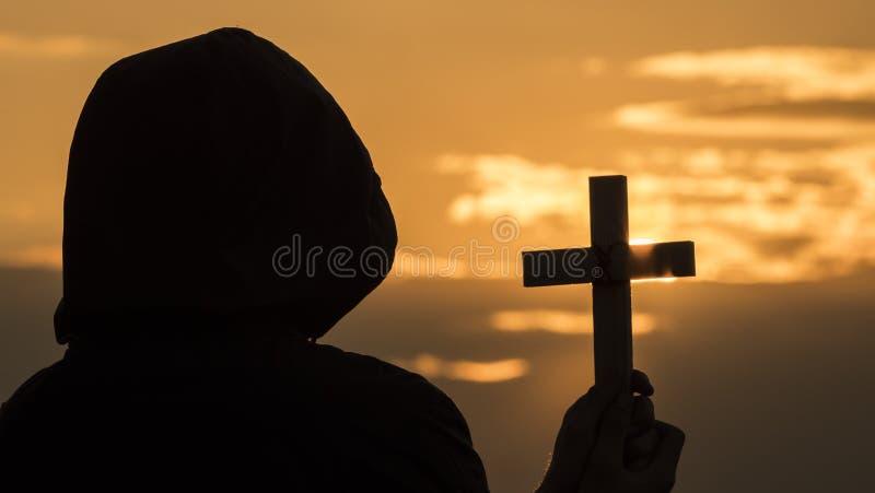 Een monnik in een kap met een kruisbeeld in zijn handen bevindt zich tegen de achtergrond van een dramatische hemel bij zonsonder stock afbeeldingen