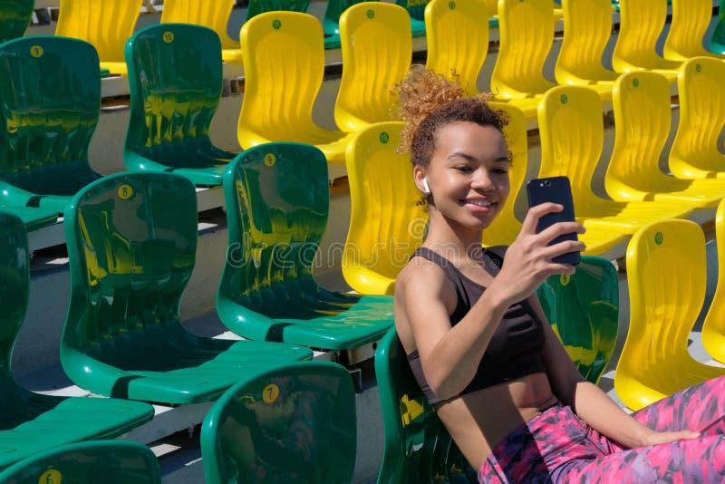 Een mooi Afrikaans-Amerikaans meisje in een zwarte T-shirt met een witte draadloze oortelefoon in haar oor zit alleen op een groe royalty-vrije stock foto