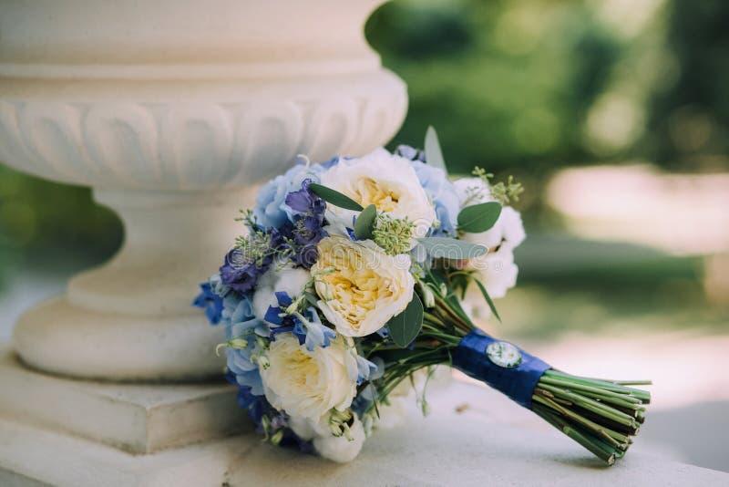 Een mooi blauw huwelijksboeket met witte pioenen, hydrangea hortensia en kamee ligt naast de marmeren vaas royalty-vrije stock fotografie