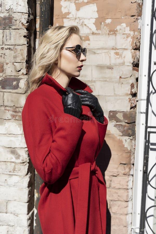Een mooi blond meisje die een rode laag, zonnebril en handschoenen dragen bevindt zich tegen een bakstenen muur die door de helde stock fotografie