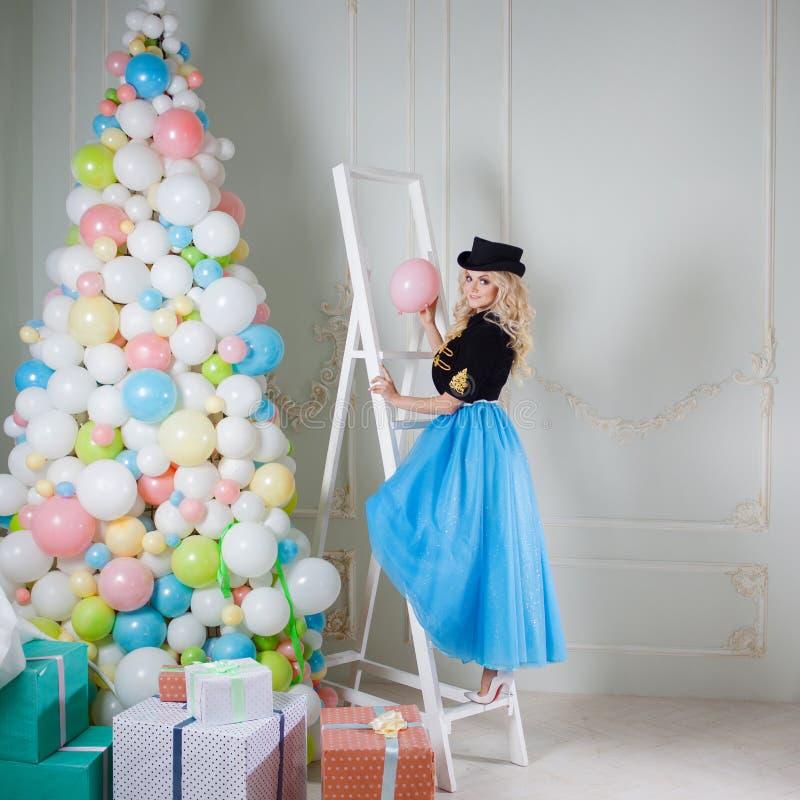 Een mooi blonde in een Carnaval-kostuum verfraait de boom van ballons Het charmeren van jonge vrouw in een curvy blauwe rok stock foto's