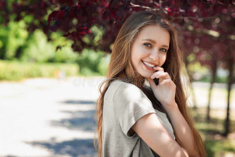 Een mooi blonde op een lichte zonnige achtergrond Een aanbiddelijk en meisje dat in openlucht ontspant lacht Een stellende jonge  stock afbeeldingen