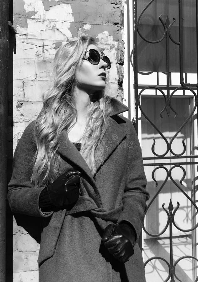 Een mooi blondemeisje die een rode laag, zonnebril en handschoenen dragen, bevindt zich door een bakstenen muur die door de helde stock afbeeldingen