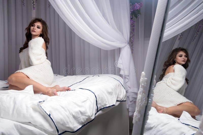 Een mooi blondemeisje in een gebreide sweater op een wit bed die haar benen buigen De bezinning is zichtbaar in de spiegel royalty-vrije stock foto's