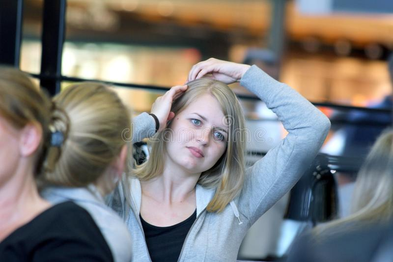 Een mooi blondemeisje neemt haar hand haar haar door royalty-vrije stock foto