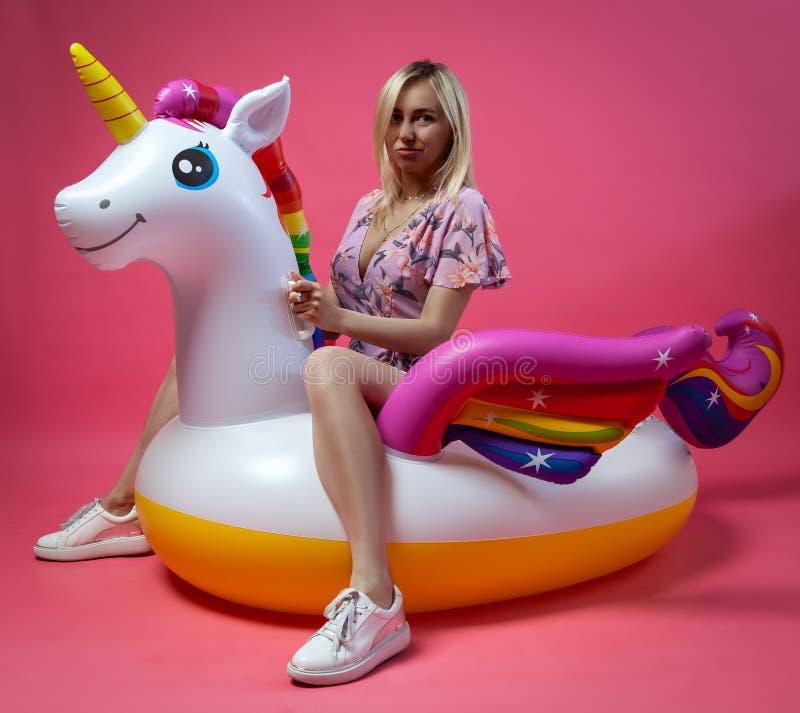 Een mooi blondemeisje in sexy sundress met slanke benen in witte tennisschoenen zit op een opblaasbare multi-colored eenhoorn op  royalty-vrije stock foto's