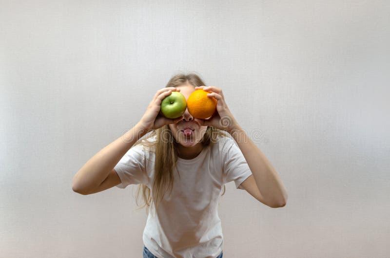 Een mooi blondemeisje in een witte T-shirt toont haar tong en houdt een appel en een sinaasappel Natuurlijke voeding voor schoolk royalty-vrije stock afbeeldingen