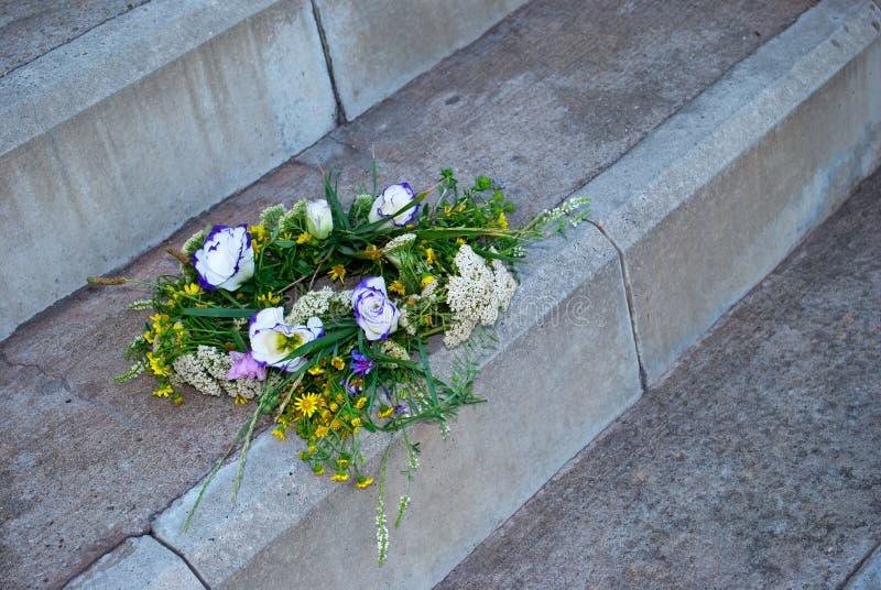 Een mooi boeket van een kroon van wilde bloemen ligt op steenstappen stock foto