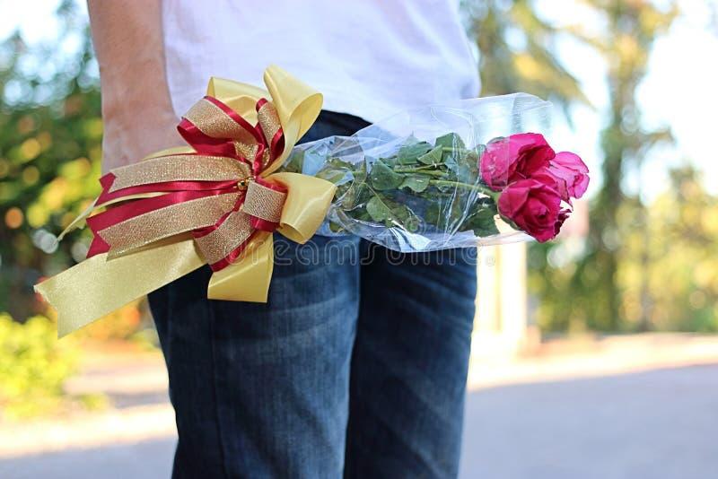 Een mooi boeket van rode rozen met lint wordt gehouden door de jonge mens met wit overhemd op aard vage achtergrond Minnaar en he royalty-vrije stock foto