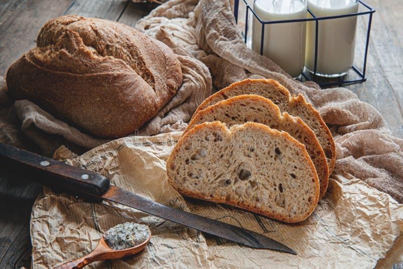 Een mooi brood van zuurdesembrood van witte tarwe op een plaat op een linnenrand Eigengemaakte Gebakjes stock foto's